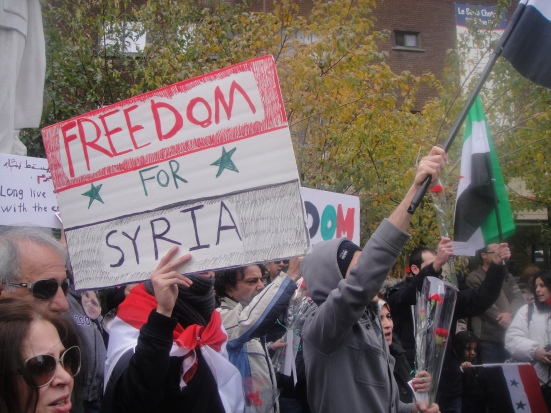 Protestors hold signs and Syrian flags. Photo by writer.
