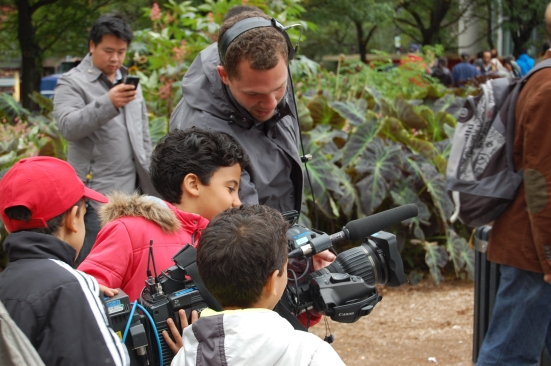 Here a radio-canada cameraman let's three young children play with his equipment.